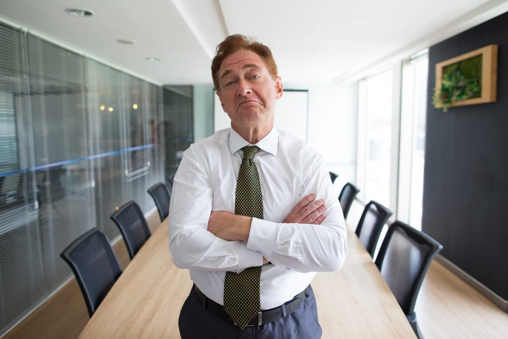 Portrait of skeptical senior Caucasian businessman wearing shirt and tie standing with folded arms and looking at camera in boardroom